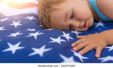 Patriotic Holiday. Cute little Child Boy with American flag. American Flag. USA Celebrate 4th of July. America Patriotic Symbols. Toddler boy laying on the american flag.  Independence Day concept.