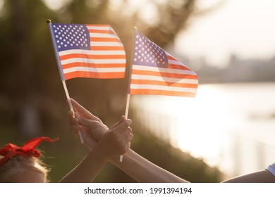 Patriotic holiday. Happy family, mother and daughter with American flag outdoors on sunset. USA celebrate independence day 4th of July.
