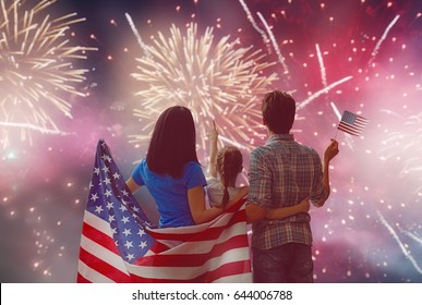 Patriotic holiday. Happy family, parents and daughter child girl with American flag outdoors. USA celebrate 4th of July.