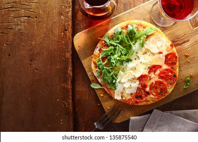 Patriotic Italian tricolore pizza with stripes of red, white and green in the colours of the national flag formed by tomato, cheese and fresh rocket leaves used for the topping on a wooden table .