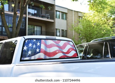 Patriotic rear window of big pick up truck, with large design of the American flag. Parked outdoors by residential area.