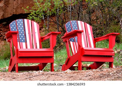 Patriotic red, white and blue Adirondack chairs sitting against a background of spring budding trees. The chairs are inviting to all celebrating summer time activities and fun in the sun.