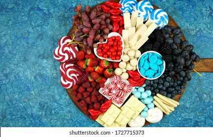 Patriotic red white and blue charcuterie dessert grazing platter with fruit, chocolate and candy for independence and national holiday celebrations. Negative copy space.