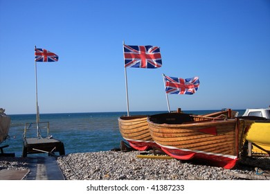 Patriotic row boats with Union Jack flags fluttering in the wind available for hire on a Devon beach