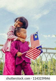 Patriotic siblings holding Malaysian flag in spirit of Merdeka (Independence Day)