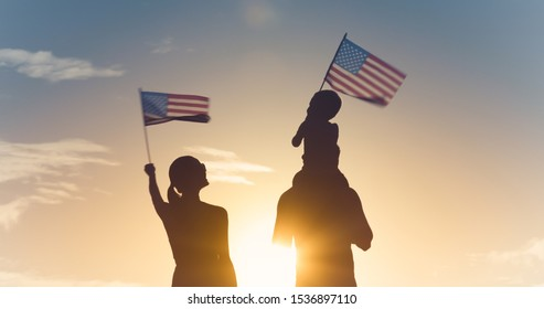 Patriotic silhouette of family waving American USA flags.