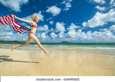 Patriotic smiling woman with american flag bikini weaving american flag. Female jumping in tropical Hawaiian beach. Lanikai Beach in Oahu, Hawaii, USA. Freedom and patriotic concept. Indipendence day.