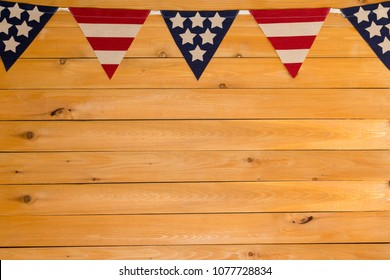 Patriotic Stars and Stripes American bunting on a garland or string as a top border on natural wood with copy space for Independence Day