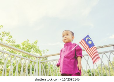Patriotic toddler with Malaysian flag in spirit of Merdeka (Independence Day)
