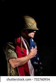 Patriotic US Marine (Vietnam War) with the American flag around his shoulders, standing against a black background.