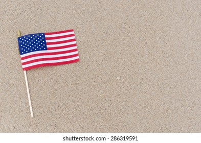 Patriotic USA background with American flag on the sandy beach
