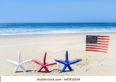 Patriotic USA background with starfishes and american flag on the sandy beach