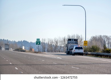 A patrol policeman on a truck with flashing lights stopped a big rig semi truck with flat bed semi trailer with commercial cargo at the exit from the highway to check logbook records