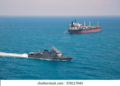 Patrol vessel sailing pass oil tanker ship