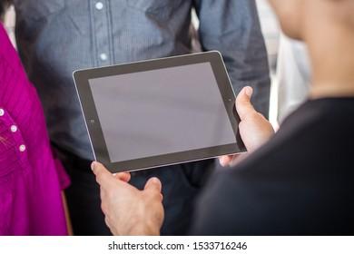 Drużyna patrzy na tablet - praca w zespole