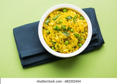 Patta Gobi Sabji OR Cabbage sabzi with green peas and curry leaves, served in a bowl over moody background, selective focus