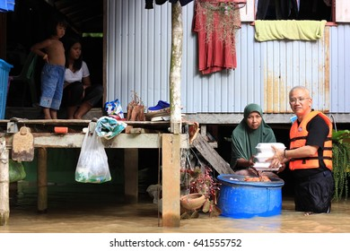 Pattani, TH - January 3 2017 : Legislators Mr.Anusarn Suwanmongkol go to flood area to help flood victims with foods and drinking water at Pakaharang and Barahor Sub-district in Pattani Thailand.