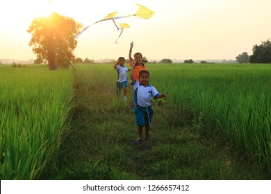 PATTANI,THAILAND  -February 2017: The children enjoy flying a kite on the fields of the countryside.