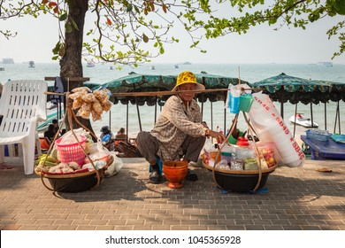 PATTAYA BEACH, CHONBURI / THAILAND - FEBRUARY 5, 2017: Local, old, female street vendor on the sidewalk at the beach in Pattaya City, Thailand on a hot day.