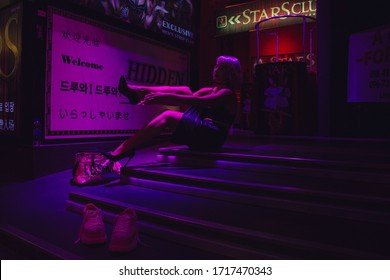 Pattaya, Chon Buri / Thailand - September, 28 2019: Stripper in Pattaya putting on her shoes before the show in night club. She wears pink blunt bob wig,  black top and black leather skirt.