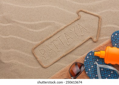Pattaya  pointer and beach accessories lying on the sand, as background