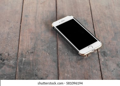 PATTAYA, THAILAND - 10 FEBRUARY 2017: Studio shot of iPhone 7 in case with selective focus on wooden table surface on Pattaya, Thailand at 10 Feb 2017. iPhone 7 is smartphone produced by Apple inc.
