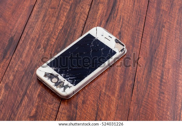 PATTAYA, THAILAND - 28 NOVEMBER 2016: Studio shot of broken mobile phone iPhone 4S with damaged screen and body on dark wooden table surface with selective focus. iPhone mobile designed by Apple