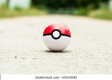 PATTAYA, THAILAND - 29 AUGUST 2016: The photo of Pokeball on asphalt road on 29 August in Pattaya, Thailand. Pokeball is equipment for catch Pokemons - characters in game Pokemon Go.
