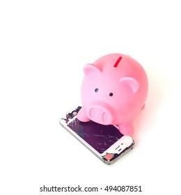 PATTAYA, THAILAND - 6 OCTOBER 2016: Studio shop of broken Smartphone of Apple Inc iPhone 4S and piggy bank on 6 oct 2016 at Pattaya, Thailand.  Selective focus