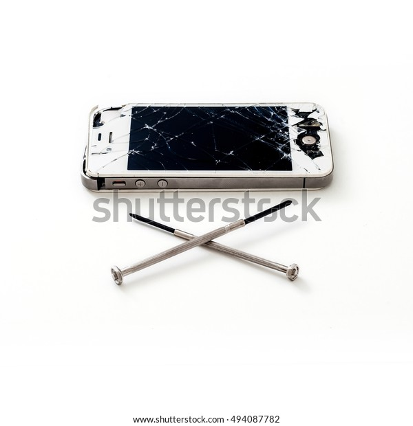 PATTAYA, THAILAND - 6 OCTOBER 2016: Studio shop of broken Smartphone of Apple Inc iPhone 4S and two screwdriver spelled as cross on 6 oct 2016 at Pattaya, Thailand. Selective focus