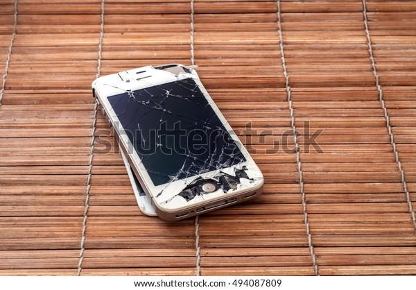 PATTAYA, THAILAND - 6 OCTOBER 2016: Studio shop of broken Smartphone of Apple Inc iPhone 4S on bamboo table on 6 oct 2016 at Pattaya, Thailand.  Selective focus