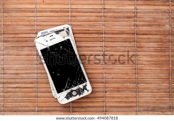 PATTAYA, THAILAND - 6 OCTOBER 2016: Studio shop of broken Smartphone of Apple Inc iPhone 4S on bamboo surface on 6 oct 2016 at Pattaya, Thailand.  Selective focus