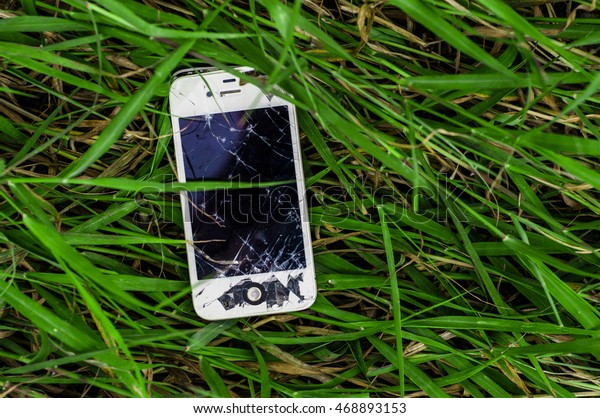 Pattaya, Thailand - August 15, 2016 Photo of a broken iPhone 4s in green grass. iPhone 4s is a smartphone developed by Apple Inc.