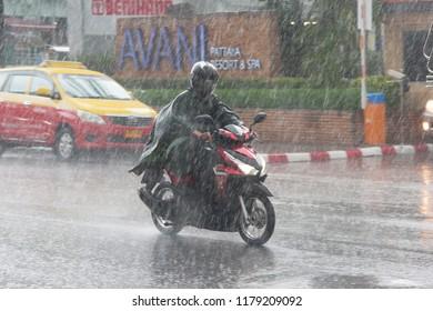 PATTAYA THAILAND - CIRCA MAY 2018.  Motorbike driver on wet Thai streets during heavy tropical storm rain. Monsoon season. Day editorial shot