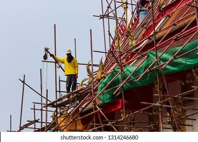 Pattaya / Thailand - February 7 2019 : Man working on Buddhist Temple roof