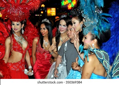"Pattaya, Thailand - January 3, 2010:   An Asian tourist poses with a group of ""ladyboy"" performers from the famed Alcazar transvestite show"