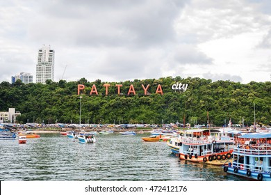 PATTAYA, THAILAND - JULY 17: Pattaya bay with commerical boats and the Pattaya City sign on the hill on July 17, 2016.  Pattaya, an hour outside of Bangkok, is famous for its beaches and night life.