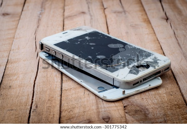 PATTAYA, THAILAND - JULY 31, 2015: Photo of a broken iPhone 4S on wooden surface on July 31,2015.