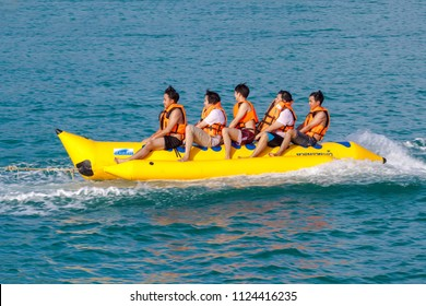 PATTAYA, THAILAND - JUNE 23: Happy people having fun riding Banana Boat near the beach in Pattaya on June 23, 2018