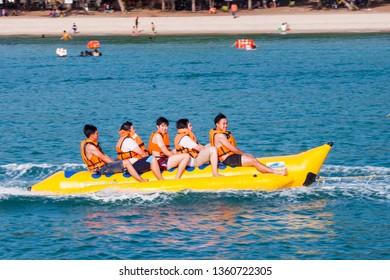 PATTAYA, THAILAND - JUNE 23: Happy people having fun riding Banana Boat near the beach in Pattaya on June 23, 2018