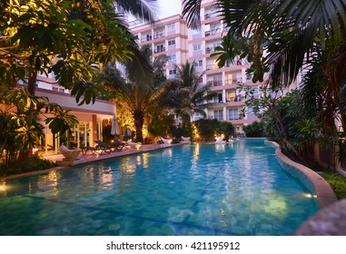 PATTAYA, THAILAND - MARCH 24, 2014:  Swimming pool on condominium area, illuminated water in evening, resort in Pattaya, Thailand