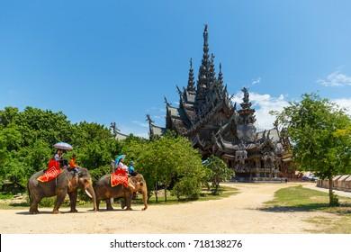 PATTAYA, THAILAND - SEPTEMBER 12, 2017: Tourists ride elephants around the Sanctuary of Truth in Pattaya