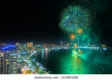 Pattaya, Thailand-JUNE 9, 2018 : Fireworks in Pattaya over cityscape near beach and sea with hotels, service boats and cruises during blue twilight time for celebrating New Year eve or special events