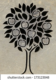 The pattern of an apple tree cut into a sheet of metal.