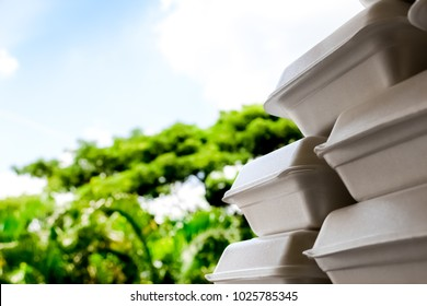 Pattern background of stacks of foam boxes on blurred tree background , environmental problem concept.
