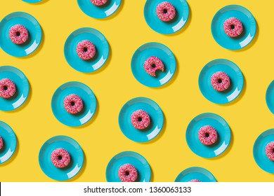 Pattern of blue plates with one pink glazed doughnut arranged and isolated on a bright yellow studio lit background.