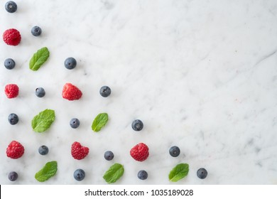 Pattern of Blueberries, Raspberries and Mint on Marble Table top with Copy Space