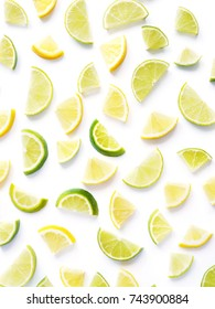 Pattern of citrus fruits. Lemon and lime slices on a white background. Top view, flat lay. Food background, wallpaper.