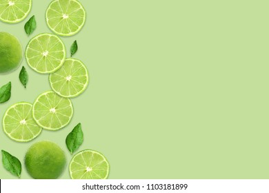 Pattern of citrus fruits.Fresh organic ripe lemon and lime with green leaves isolated on green background.Top view,flat lay with copy space empty blank for text.Food background, wallpaper.