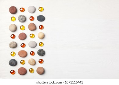 pattern of colored pebbles and orange glass beads on white wooden background. Meditation and calmness concept. Flat lay, top view. copy space
